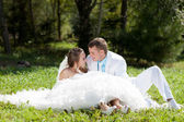 Bride and groom huggling sitting at green grass — Stock Photo