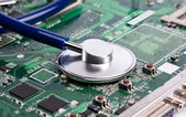 Laptop motherboard with stetoscope — Stock Photo