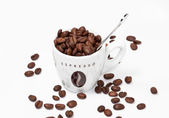 Coffe cup full of beans and spoon — Stock Photo