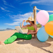 Woman with colorful balloons using laptop on the beach — Stock Photo