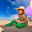Womwith colorful balloons using laptop on beach — Zdjęcie stockowe #9549499
