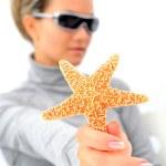 Girl with sunglasses and starfish — Stock Photo