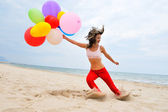 Young woman with colorful balloons on the beach — Stock Photo