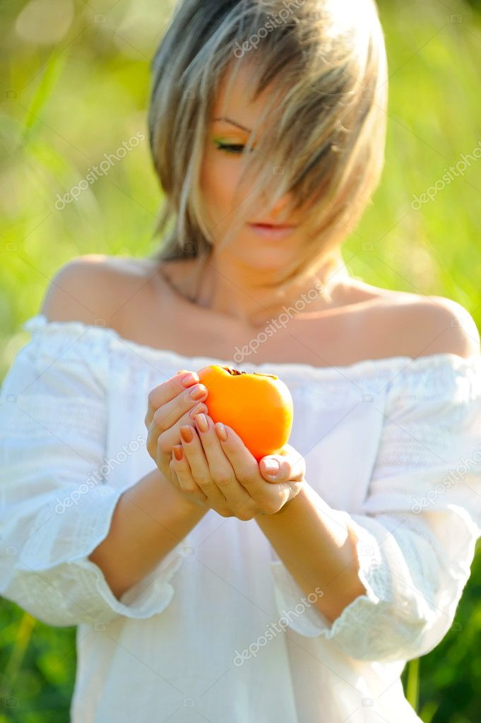 Beautiful young woman holding persimmon outdoor — Stock Photo #9549455