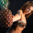 Beautiful girl holding a pineapple — Stock Photo