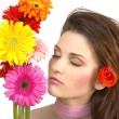 Beautiful young woman with flowers — Stock Photo