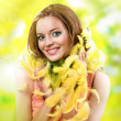 Easter picture of young woman with yellow feathers against green background — Stock Photo