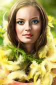 Easter picture of young woman with feathers green background — Stock Photo