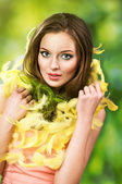 Easter picture of young woman with feathers against green background — Stock Photo