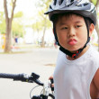 Cycling boy stick out tongue — Stock Photo