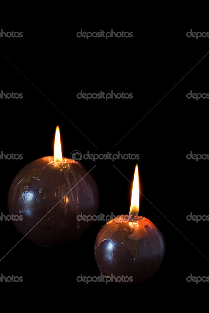 Two round brown burning candles against a black background — Photo #9931211