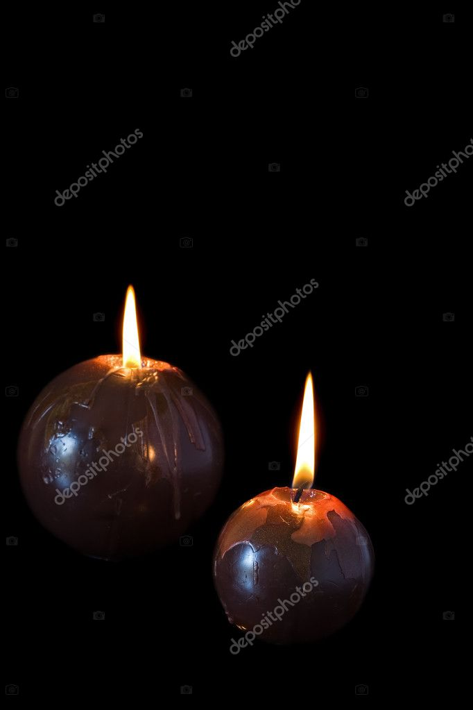 Two round brown burning candles against a black background — Foto de Stock   #9931211