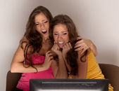 Gemini sisters watching a horror movie on TV — Stock Photo