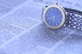 Wrist watch over newspaper — Stock Photo