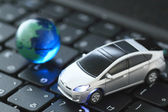Glass globe and toy car over keyboard — Stock Photo