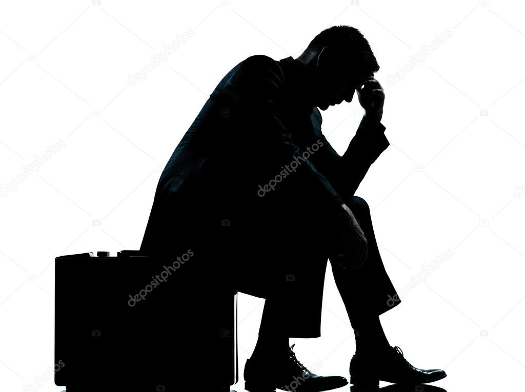 One business man sitting on suitcase tired despair silhouette stock