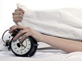 Woman in bed awakening tired holding alarm clock — Stock Photo