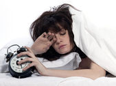 Woman in bed awakening tired holding alarm clock — Stock Photo