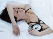 Woman in bed sleeping with an alarm clock — Stock Photo