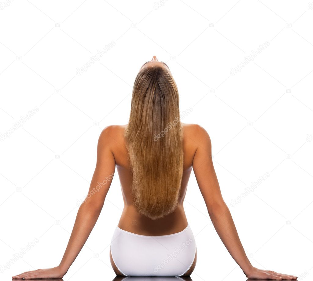 Rear view of a long blond haired young woman stretching backwards isolated on white background — Stock Photo #8999070