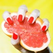 Stock Photo: Woman Hand Squeezing a grapefruit
