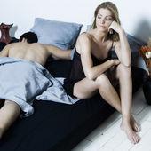 Par i en säng sömnlöshet kvinna vaken man sover — Stockfoto