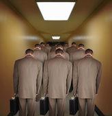 Przepracowany biznesmenów, schodząc w dół korytarz — Zdjęcie stockowe