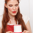 Woman blowing out a candle — Stock Photo