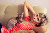 Woman with cat laying on a sofa — Stock Photo