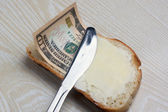 Butter and money on a slice of bread — Stock Photo