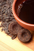 The cup of pu-erh and two bricks — Stock Photo
