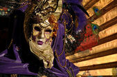 Venetian Mask dressed in violet with golden Fan — Stock Photo