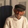 Elderly fisherman in front of the door in a greeck island — Stock Photo