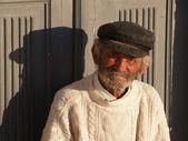 Elderly fisherman in front of the door in a greeck island — Stock Photo