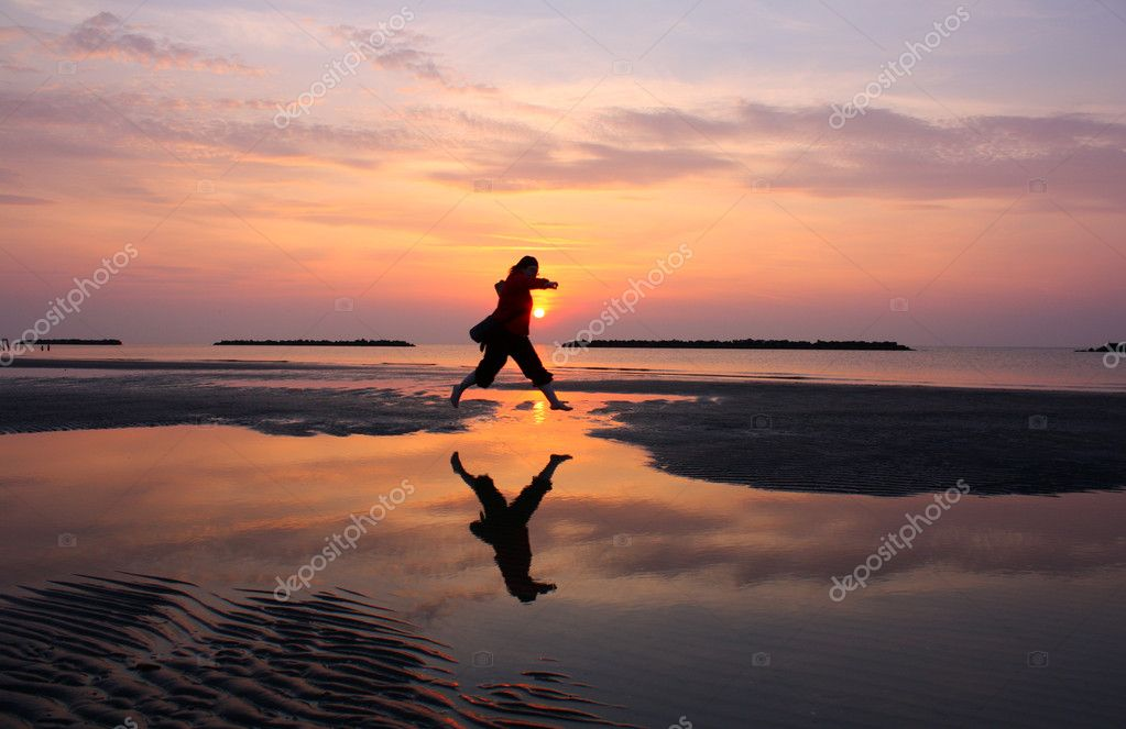 Silhouette of a girl running on beach at dawn to the sea — Stock Photo #9136628
