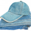 The blue denim baseball cap on a heap of blue jeans. — Stock Photo