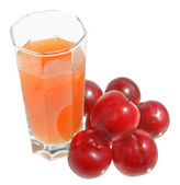 A glass of plum juice with heap of plum top view — Stock Photo