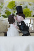 Kissing bride and groom figurines — Stock Photo