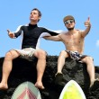 Two friend surfer sitting on a rock — Stock Photo