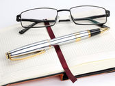 Notebook with pen and glasses — ストック写真