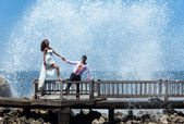 Happy young couple walking on the old pier — Stock Photo