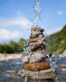 Pyramid of stones beside a mountain river — Stock Photo