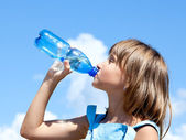 Young beautiful girl drinking water — Stock Photo