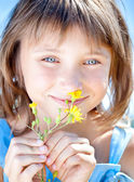 Happy little girl with a flower in his hand — Стоковое фото
