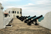 Cannons along wall at Cape Coast castle #2 — Stock Photo
