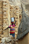 Dogon woman carrying bucket and child in Mali — Stock Photo