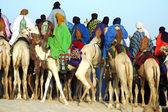 Man riding behind a group of Tuareg on camels — Stock Photo