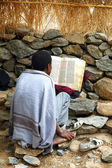 Young priest reading from bible — Stock Photo