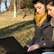 Young girls using laptop outdoor — Stock Photo
