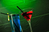 A red cocktail and a blue longdrink on a green background — Stock Photo